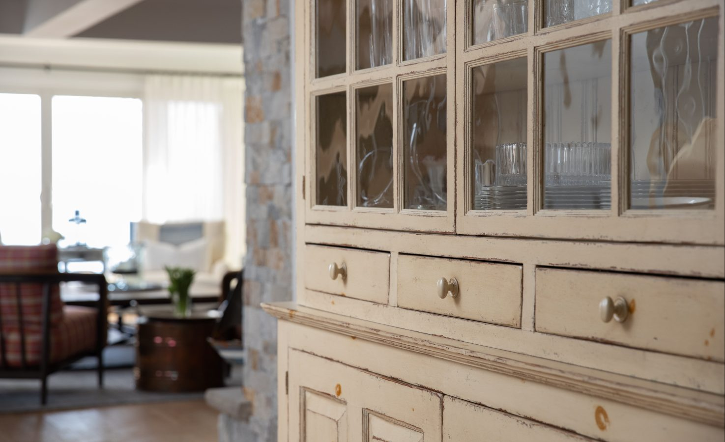Close up of beige glass cabinet, beyond it looking into living space