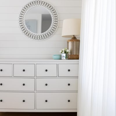 White dresser in corner of room displaying a lamp and white flowers. Mirror is on the wall above the dresser.