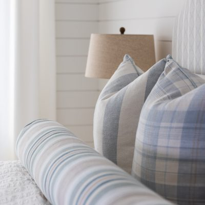 Close up of decorative plaid pillow on bed
