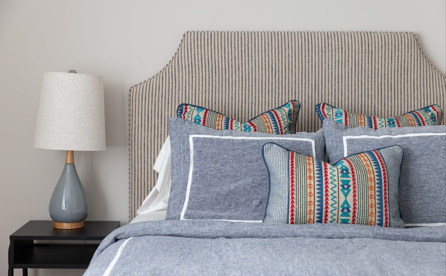 View of bed with grey sheets and colourful decorative pillows, beside side table with lamp